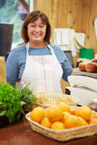 Female Sales Assistant At Checkout Of Farm Shop Stock Photography
