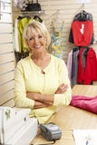 Female sales assistant in clothing store Stock Images