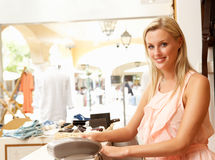 Female Sales Assistant In Clothing Store Stock Image