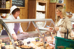 Female Sales Assistant Serving Customer In Delicatessen Royalty Free Stock Image