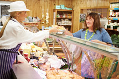 Female Sales Assistant Serving Customer In Delicatessen Royalty Free Stock Images