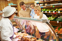 Female Sales Assistant Serving Family In Delicatessen. Female Sales Assistant Serving Young Family In Delicatessen Stock Images
