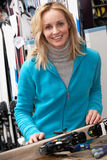 Female Sales Assistant With Skis In Hire Shop. Smiling At Camera Stock Photo