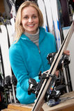 Female Sales Assistant With Skis In Hire Shop. Smiling Royalty Free Stock Images
