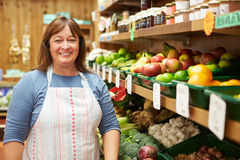 Female Sales Assistant At Vegetable Counter Of Farm Shop Royalty Free Stock Photos