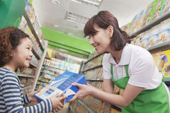 Female Sales Clerk Gives Little Girl Cereal Box.  Stock Photos