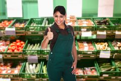 Female sales clerk showing thumb up gesture Stock Image