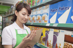 Female Sales Clerk Working in a Supermarket Royalty Free Stock Images