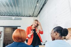 Female Sales Consultant telling about new goods to young business women. Attractive Female Sales Consultant in red jacket telling about new goods to young royalty free stock photos