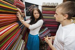 Female salesperson assisting man in textile store Stock Photos