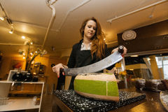 Female salesperson cutting cheese at store Stock Images