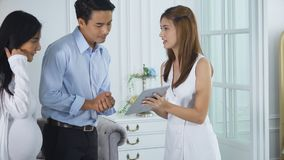 Female salesperson invite the furniture to the spouse. The spouse walking into the showroom, beautiful female sales is using the tablet to the client product Royalty Free Stock Photo