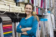 Female saleswoman, interior designer in showroom. Female saleswoman, interior designer posing in showroom, background of book and hanger with fabric samples stock image