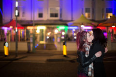 Female Same Sex Couple Kissing Outdoors at Night Stock Images
