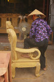 Female sanding a wooden chair Royalty Free Stock Photography