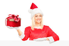 Female santa behind billboard holding a gift Royalty Free Stock Image