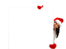 Female Santa with billboard. Female Santa with red hat and gloves behind a white billboard Stock Image