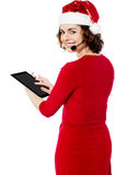Female santa browsing on her tablet pc Royalty Free Stock Photo