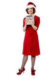Female in santa cap using tablet pc Royalty Free Stock Images