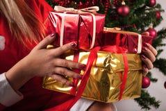 Female Santa Claus holding Christmas gift boxes Stock Photo