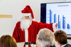 Female Santa Claus presenting in business meeting Stock Image