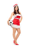 Female in Santa costume holding a football Royalty Free Stock Image