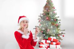 Female santa with finger on lips standing near gifts and christmas tree. Against white background Royalty Free Stock Images