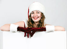 Female santa holding a christmas white card Royalty Free Stock Image