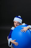Female Santa with large blue sphere Royalty Free Stock Photos