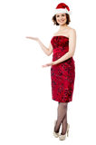Female santa showing welcome gesture Stock Photography