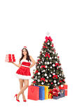 Female Santa standing by a Christmas tree Royalty Free Stock Image
