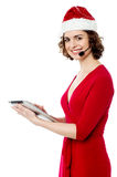 Female santa using her new tablet pc Royalty Free Stock Image
