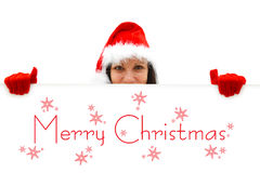 Female Santa wishing Merry Christmas. Female Santa with red hat and gloves over a white billboard, Merry Christmas is written on it Royalty Free Stock Photography