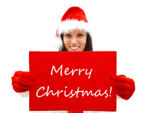 Female Santa wishing Merry Christmas. Female Santa with red hat and gloves over a red sign, Merry Christmas is written on it Royalty Free Stock Photography