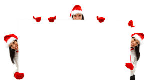 Female Santas over a billboard. Three female Santas with red hat and gloves over a white billboard Royalty Free Stock Image