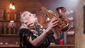 Female saxophonist performs a song in a small jazz cafe. Singing at a private jazz party. Bartender enjoying the music stock video