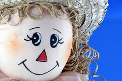 Female Scarecrow Face. Closeupe of a cute, smiling girl scarecrow.  On a blue background Royalty Free Stock Photos