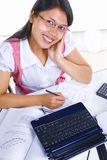 Female scholar looking at camera while studying Stock Image