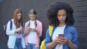 Female school pupils scrolling smartphones outdoors, gadget addiction, internet. Stock footage stock video footage