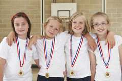 Female School Sports Team In Gym With Medals Stock Photo