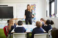 Female school teacher standing in a classroom gesturing to schoolchildren, sitting at a table listening stock photo