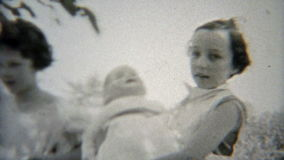1937: Female schoolmates playing doll outdoor backyard. stock video