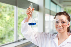 Female science student holding a blue liquid Stock Images