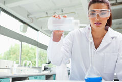 Female science student pouring liquid Royalty Free Stock Photo
