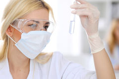 Female scientific research team with clear solution in laboratory Royalty Free Stock Images
