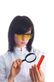 Female scientist. Looking at tube through magnifying lens Royalty Free Stock Photos