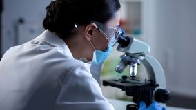 Female scientist analyzing sample under microscope, microbiology research stock photos