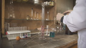 Female scientist in a bathrobe puts experiments using chemical utensils. She stands near table to work with chemical agents, its surface is covered with stock video footage