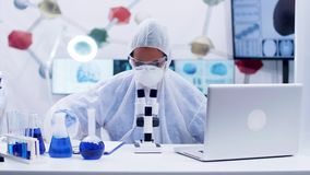 Female scientist in coverall equipment working in chemistry laboratory. Blue liquid chemical reaction stock footage