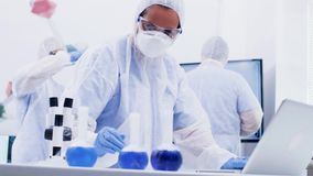 Female scientist in coverall equipment working on computer in a modern science laboratory. Scientist typing research raport on laptop stock footage